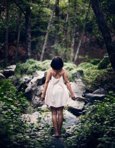 Frau mit weißem Kleid steht im Wald