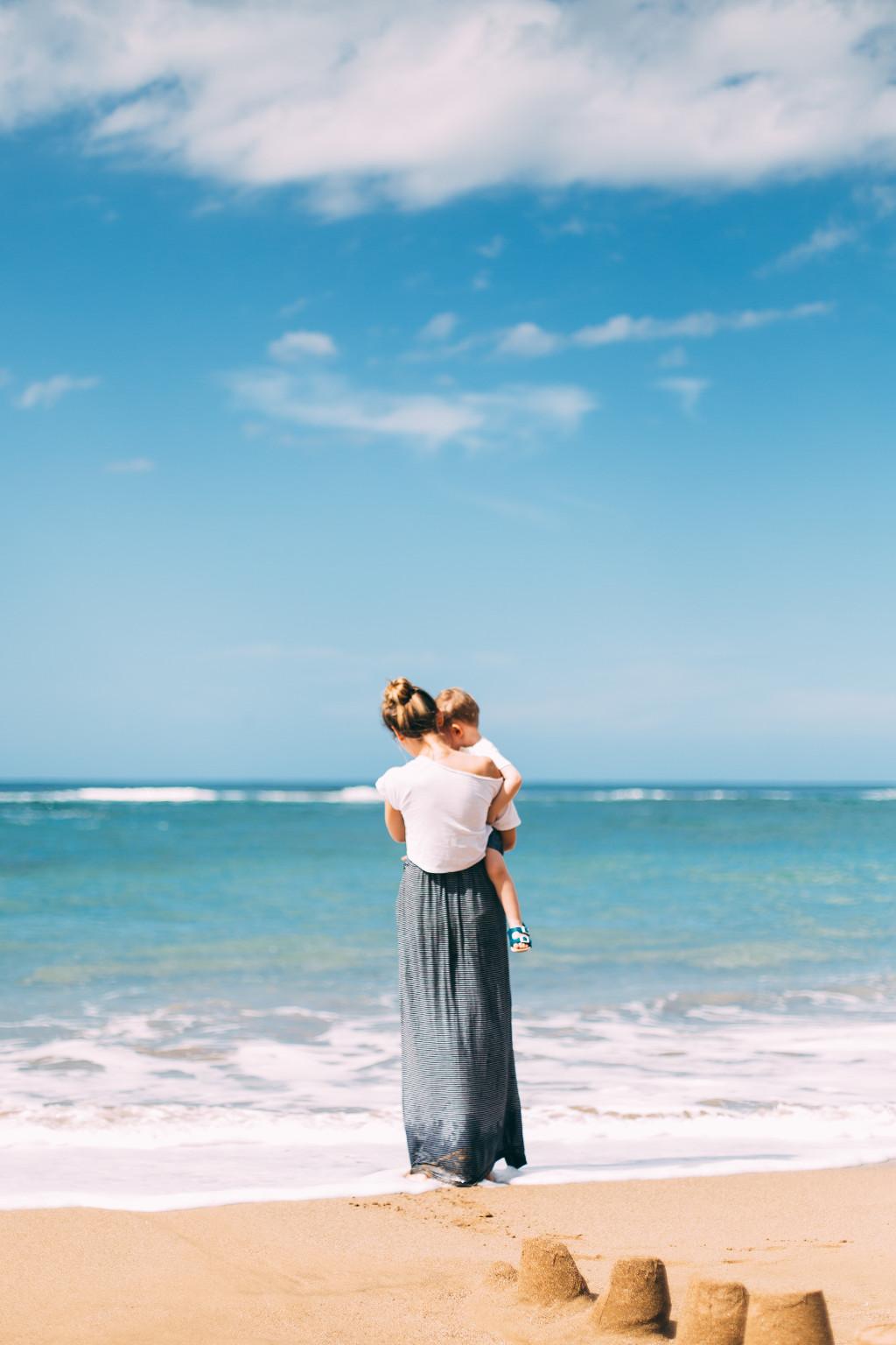Mutter hält Kind auf dem Arm am Strand