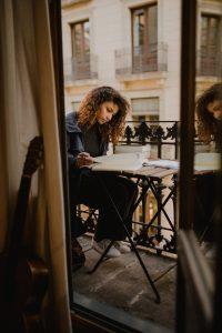 Frau sitzt auf dem Balkon und schreibt