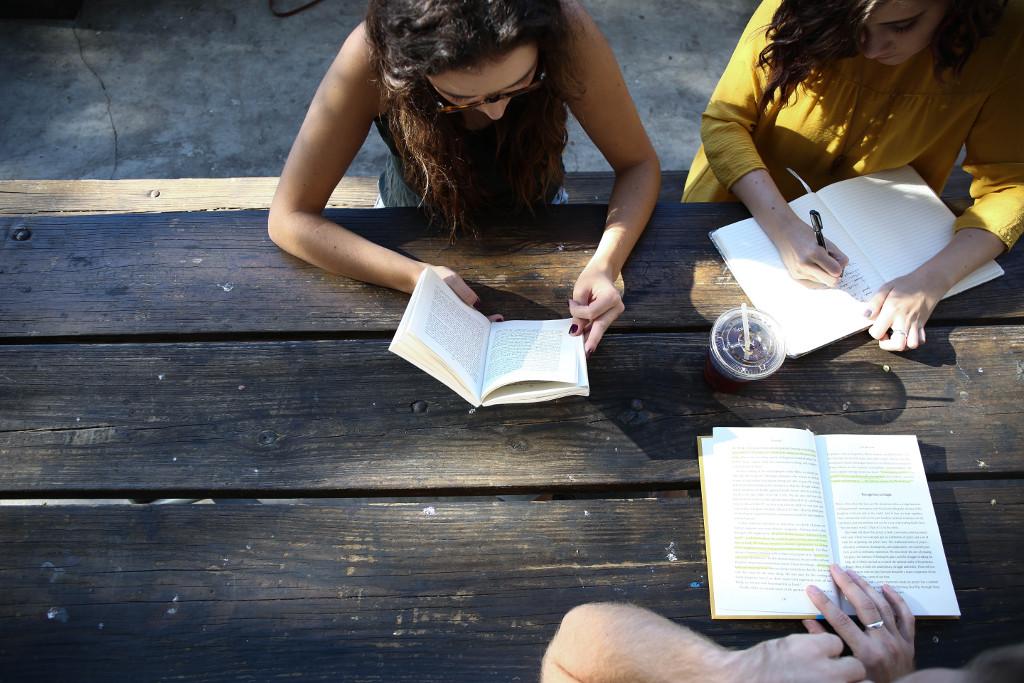 Menschen sitzen mit Büchern an einem Holztisch