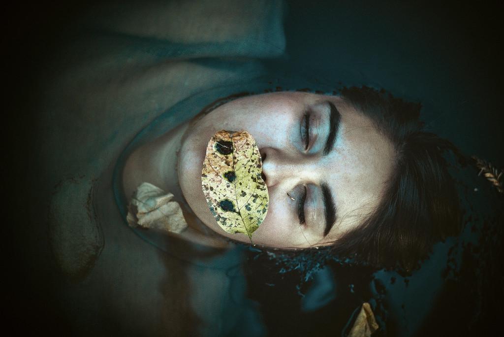 Frau mit geschlossenen Augen und Blatt auf Mund