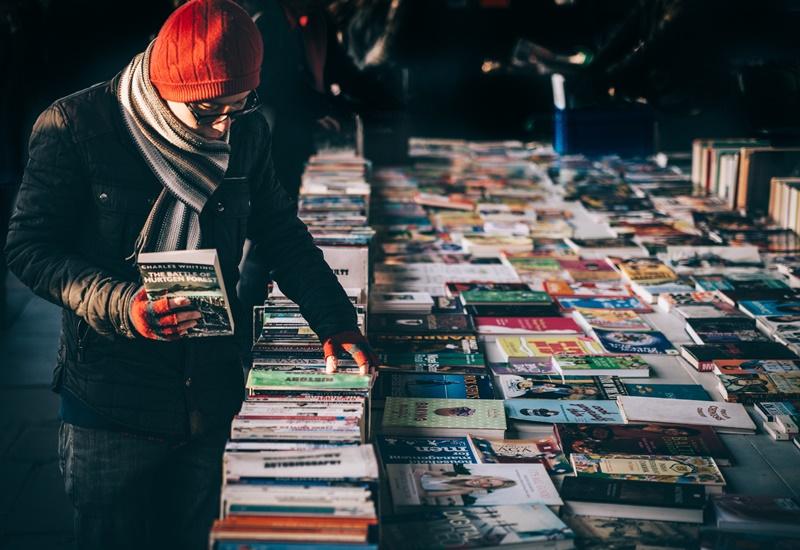 Mann steht an Buchverkauf und stöbert