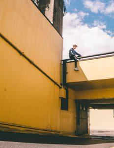 junger Mann sitzt auf Brücke