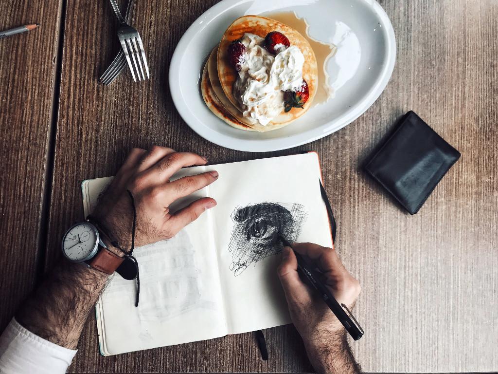 Hände, die zeichnen und Pancakes