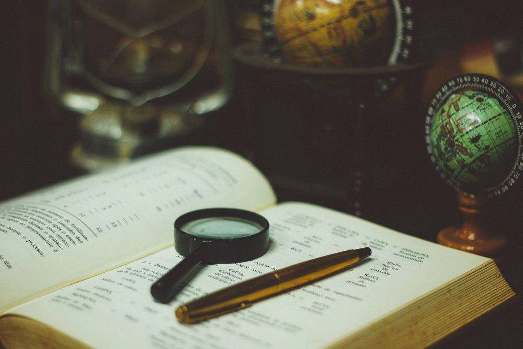 Lupe und Stift auf Buch