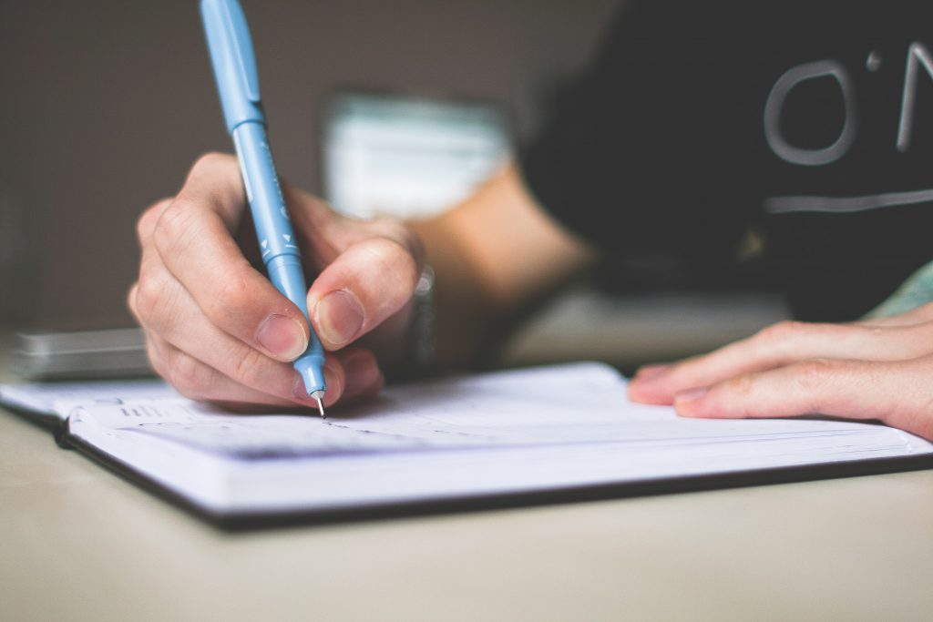 schreibende Hand mit blauem Stift