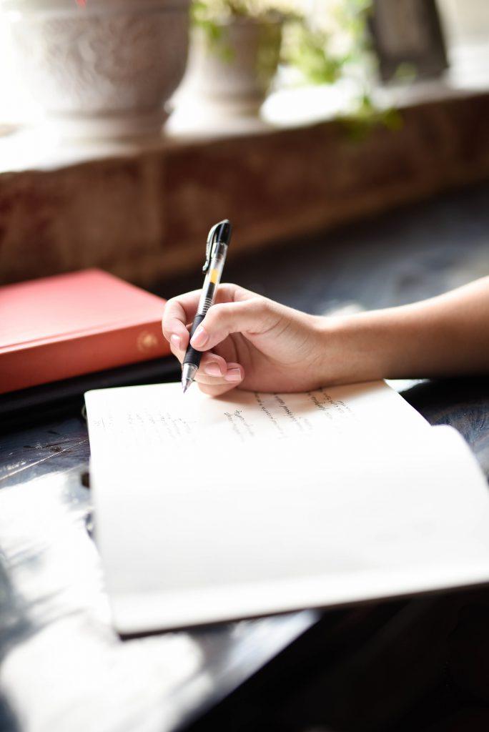 Notizbuch und schreibende Hand
