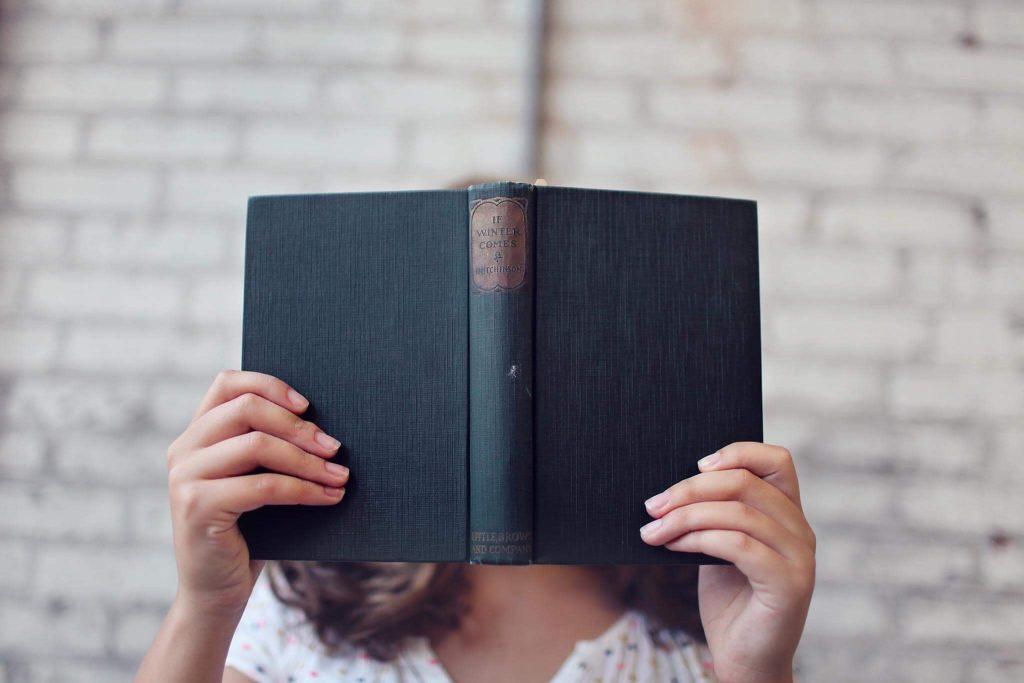 Frau hält ein Buch vor ihr Gesicht